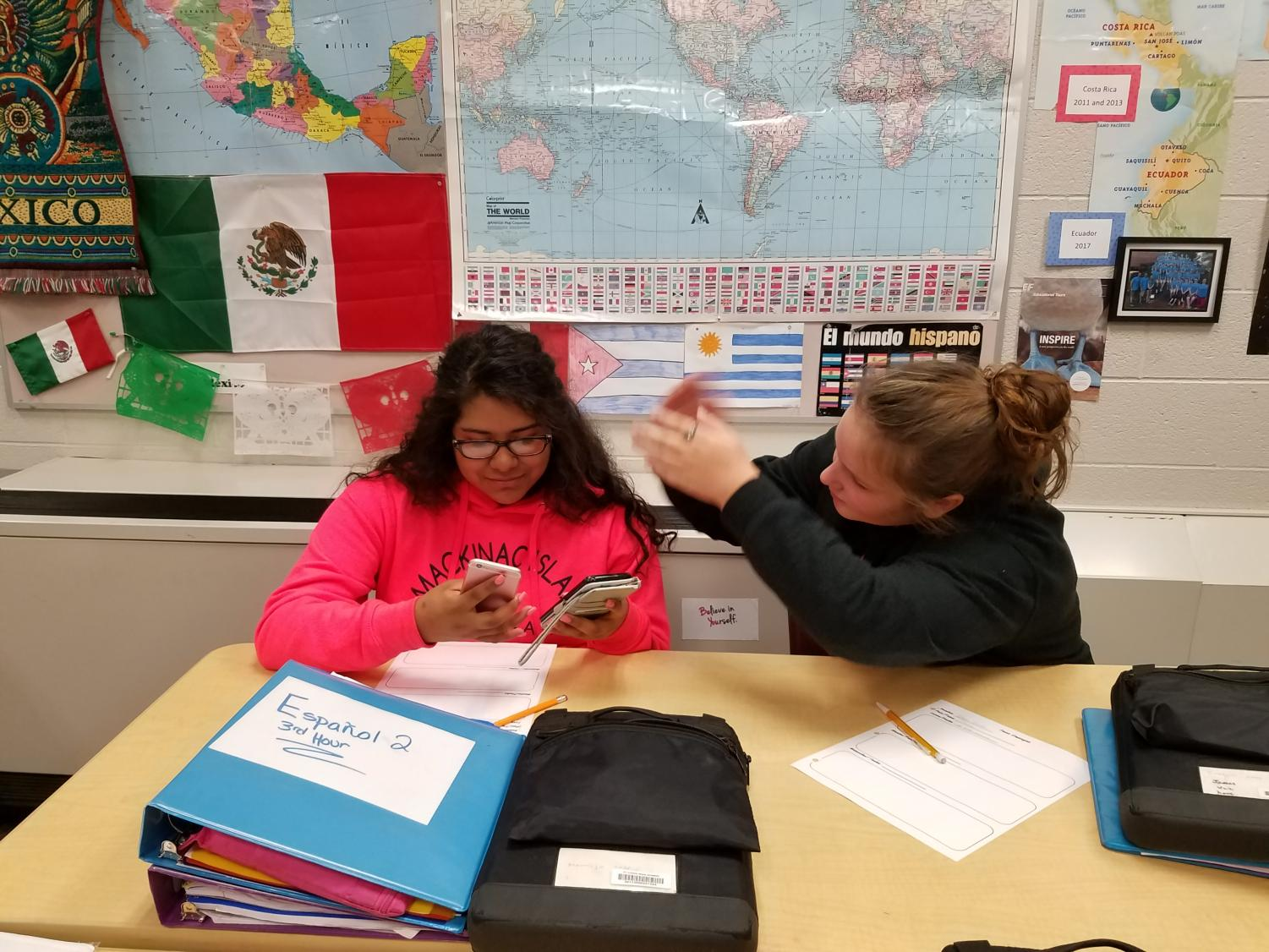 Valentina Memije (left) is too distracted by her phones to see her classmate asking for help.