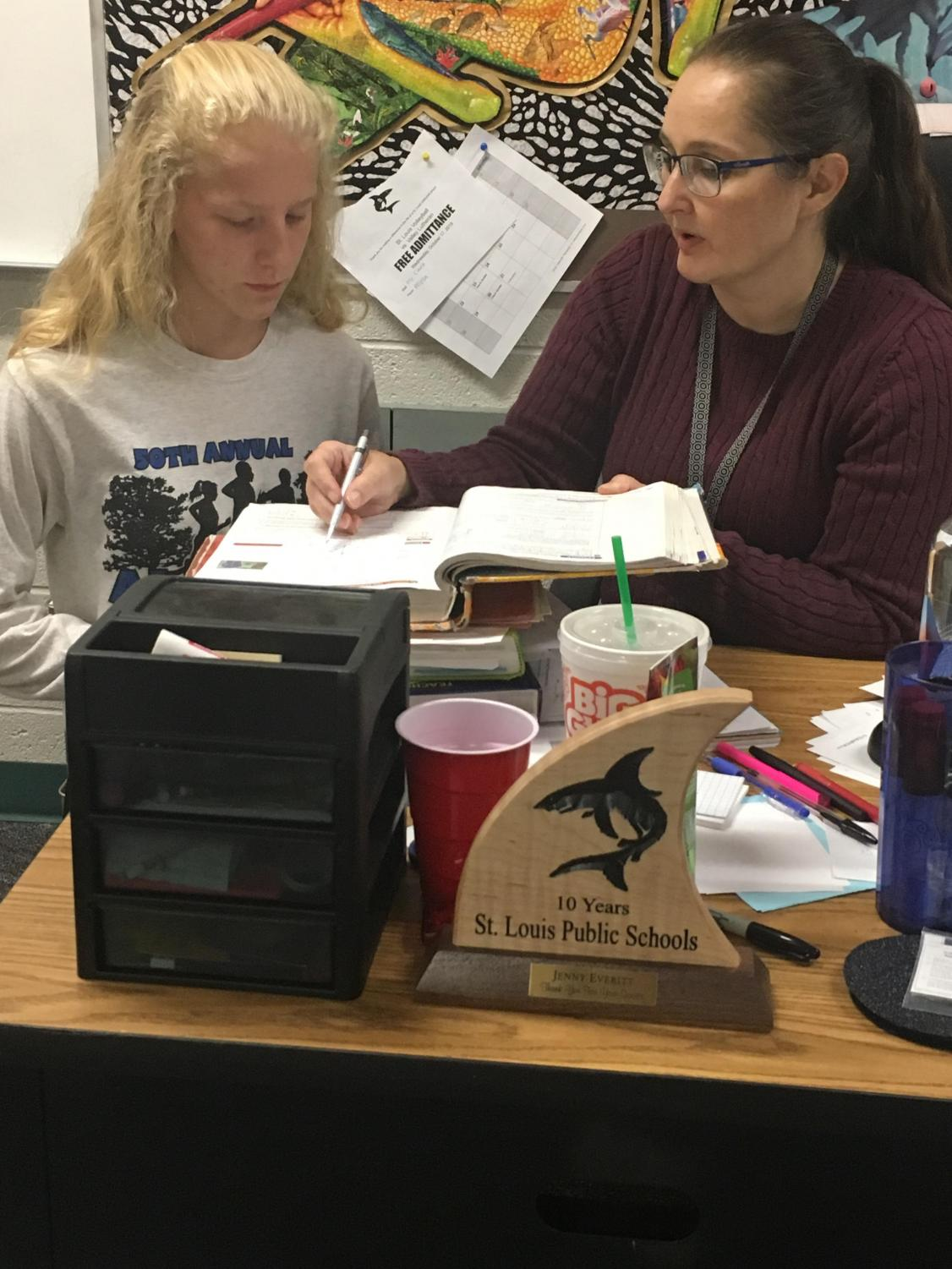 Ms. Everitt helps a student with their classwork.