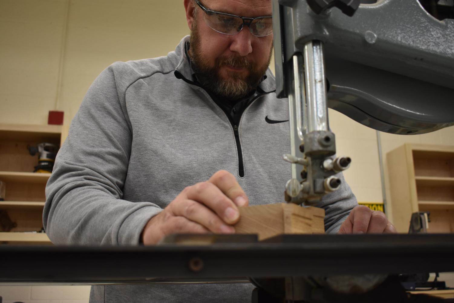 Mr. Maxwell, the woodshop instructor, makes fine-tuned adjustments on a wooden toy.
