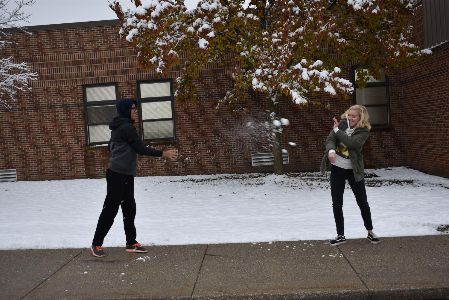 Gui (left) enjoys the early snowfall in St. Louis, and he shows it by throwing a snowball at Freja (right).