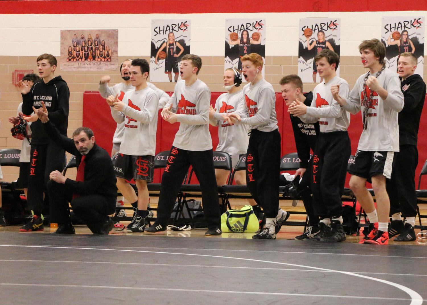Members of the 2018 Shark wrestling team celebrate during the district finals against Montabella.