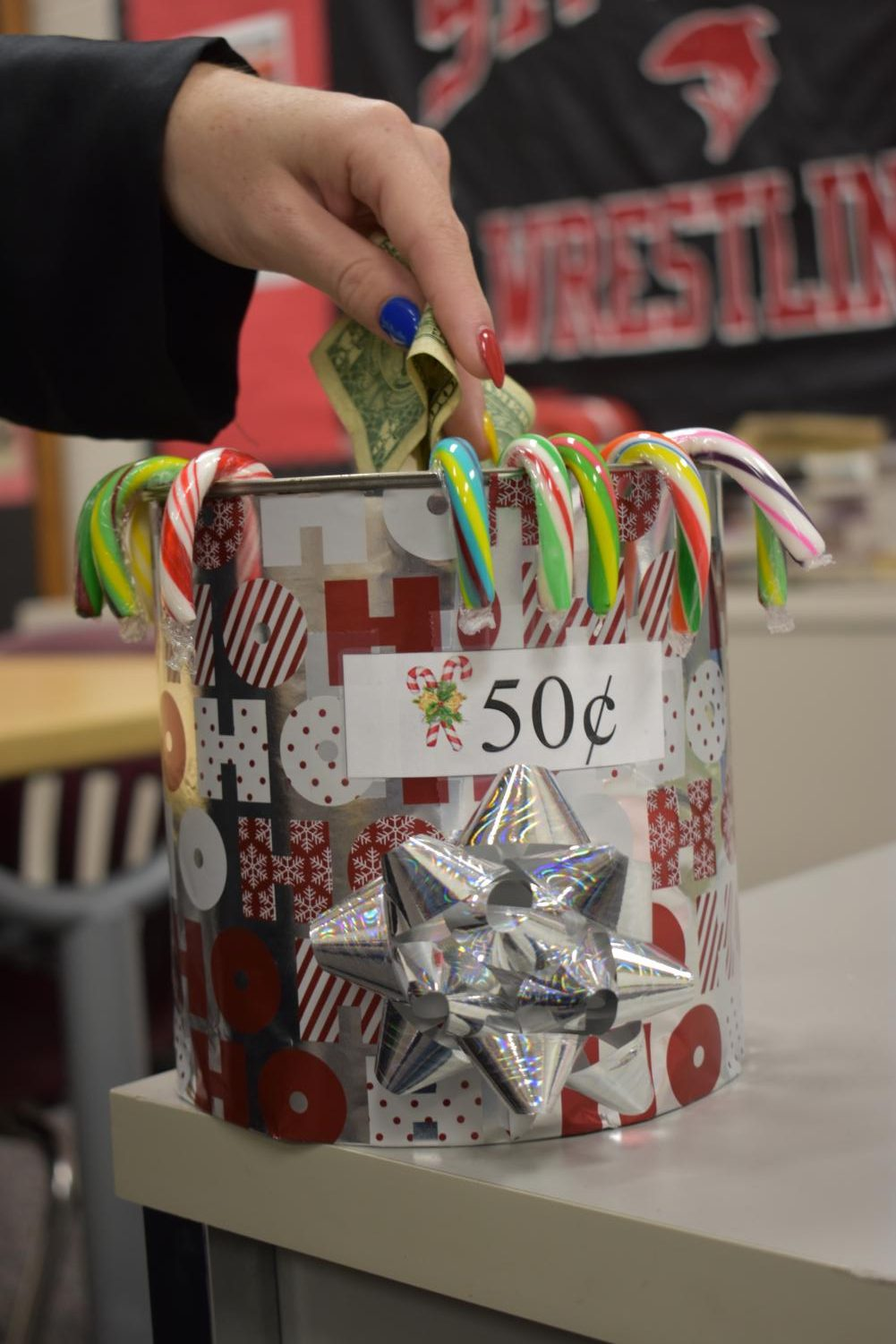 Student buys a candy cane from the bucket in a classroom.