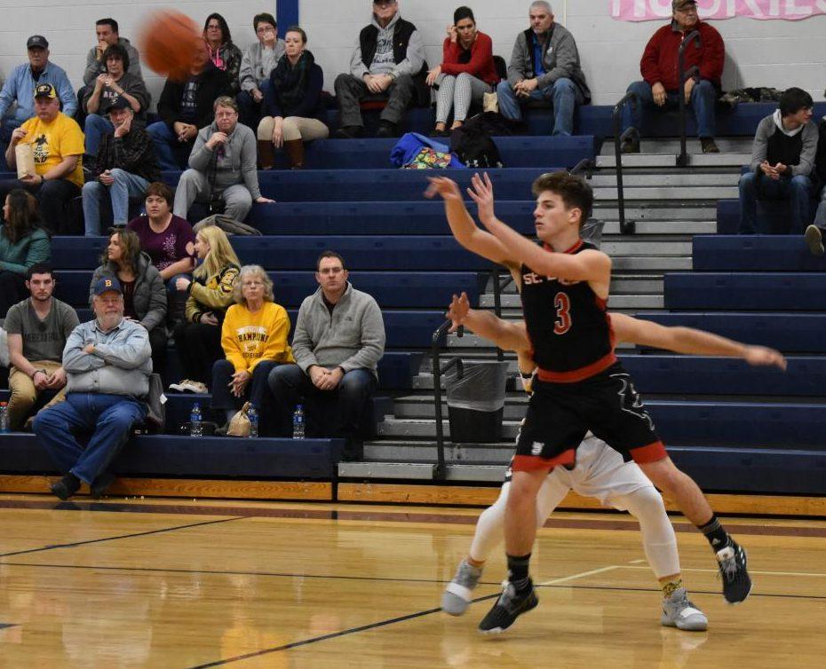 Cade Pestrue passes the ball to a team member.