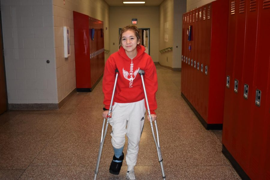 Mackenzie+Allbee+travels+through+the+hallway+using+crutches.