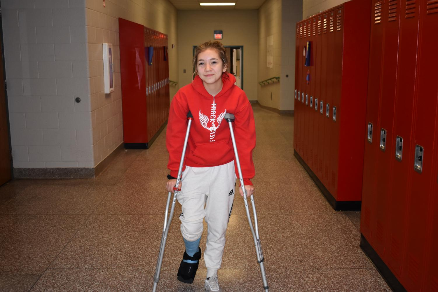 Mackenzie Allbee travels through the hallway using crutches.