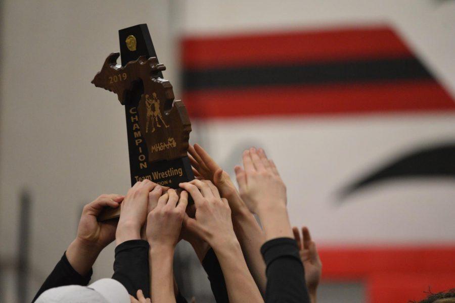 St.+Louis+wrestlers+hoist+their+Division+champion+trophy.