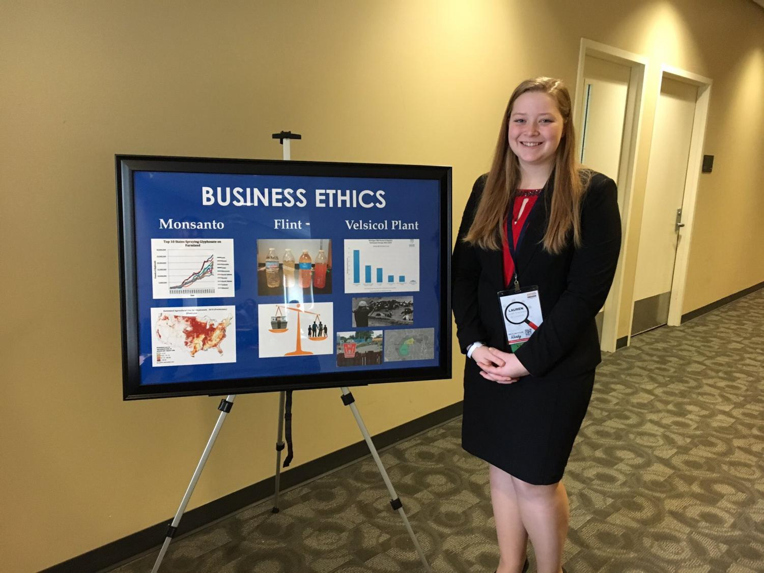Lauren Sherwood poses next to the visual aid she used for her award-winning speech.