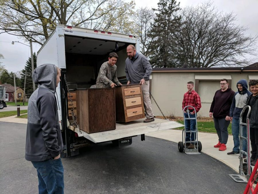 Woodshop members unload cabinets that they made for Schnepp Senior Care and Rehab Center.