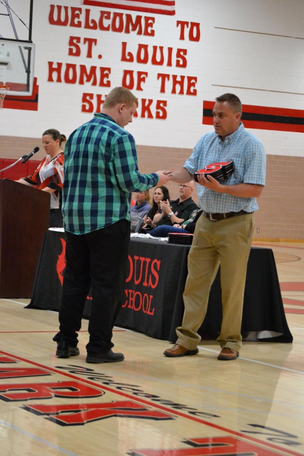 Cole Acker receives his academic letter from Mr. Hemker.