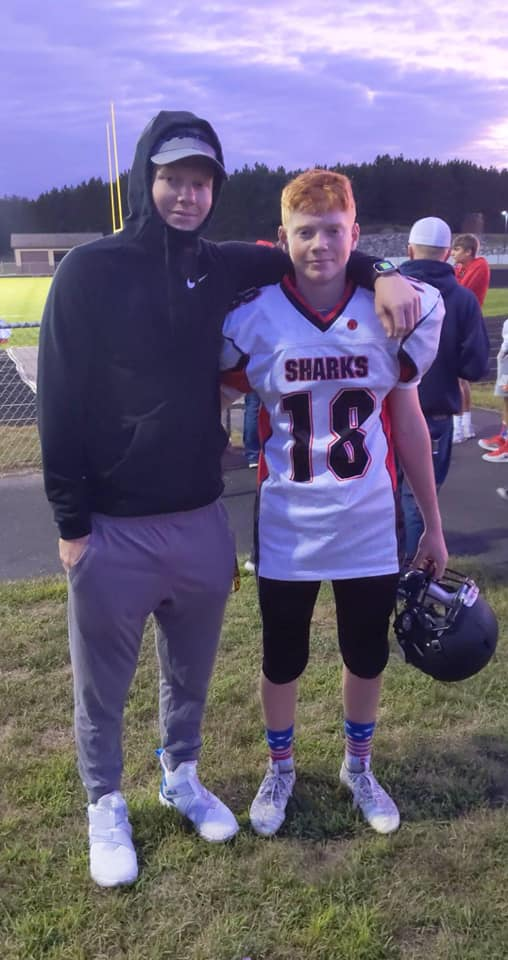 Reece Giles (right) poses with older Brother Maverick following his first start as quarterback.