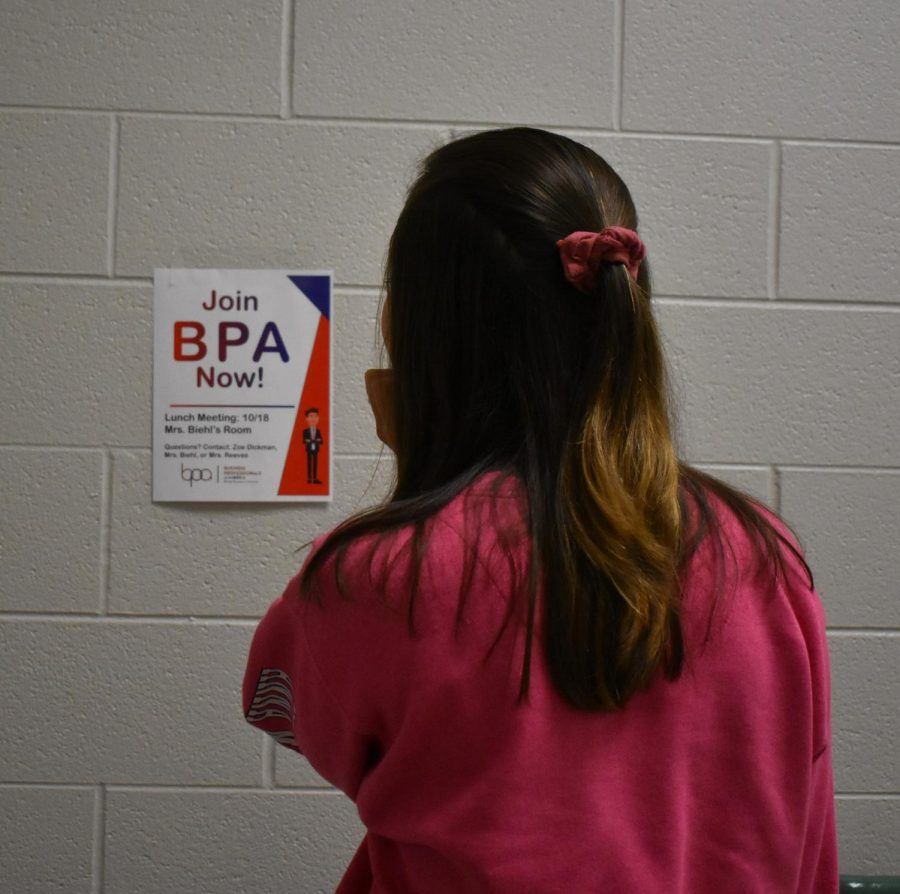 A+student+examines+a+poster+for+a+BPA+meeting.
