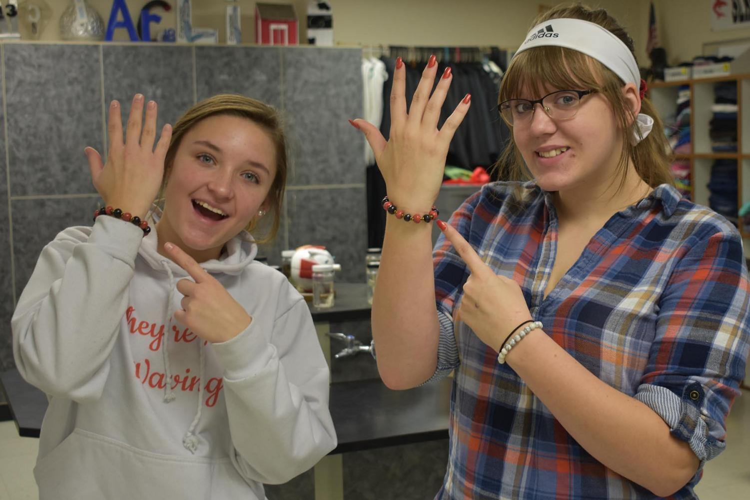 Danielle Weller (left) and Kira Dowell enjoy their Shark bracelets from the 4North project.