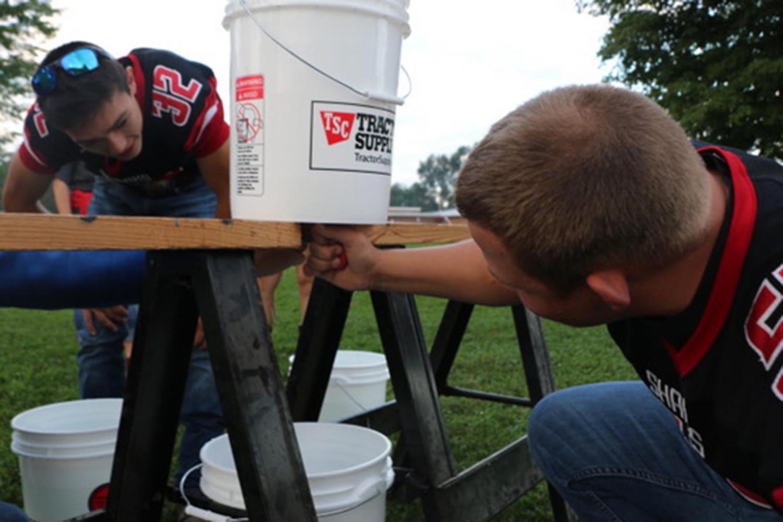 Alex Wonsey (left), looks on as a classmate drains cider.