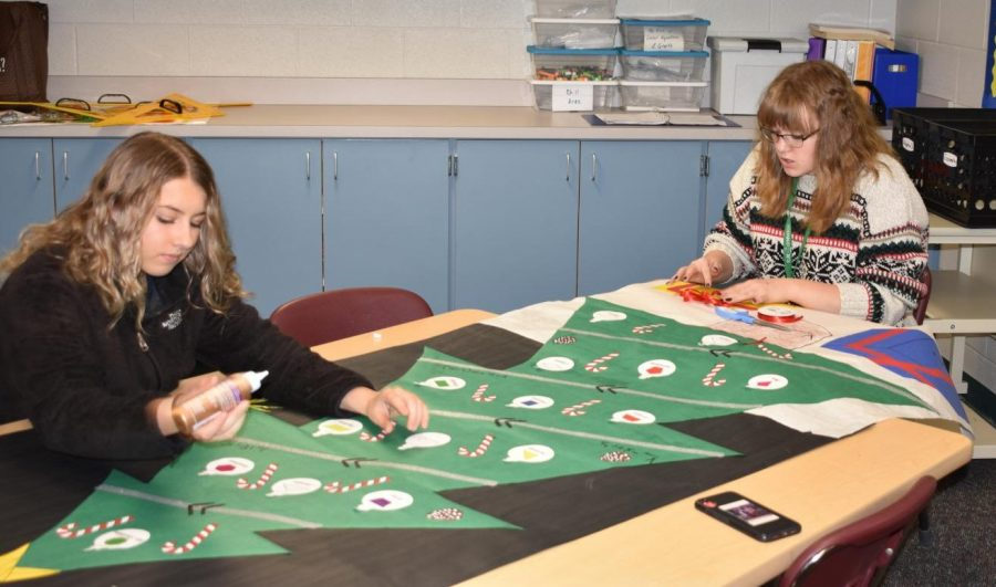 Brooke Erskin, left, and Kira Dowell, right, work on their door decoration for Shark Wars.