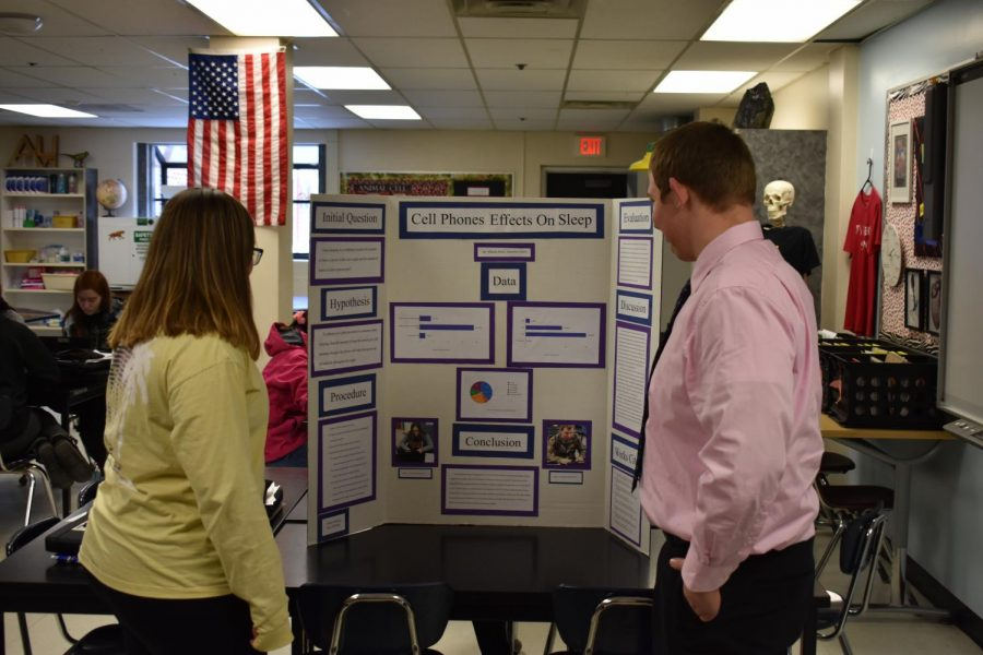 Two students analyze a board from last year as they begin their own research projects.