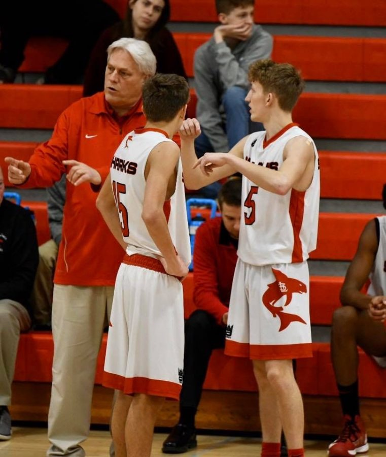 Coach+Doug+Knauf+discusses+a+play+with+seniors+Sam+Bebow+%28left%29+and+Noah+Prestage+%28right%29.