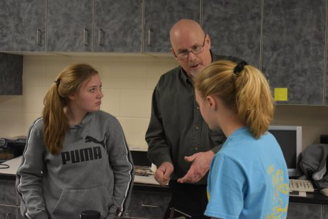 Mr. Stedman helps two students.