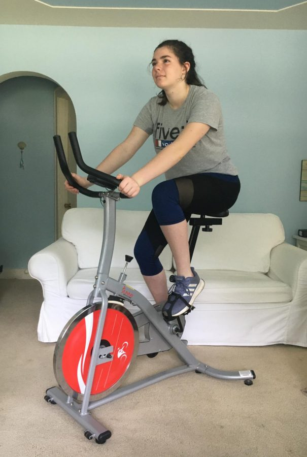 Korah Honig does a workout on a stationary bike.