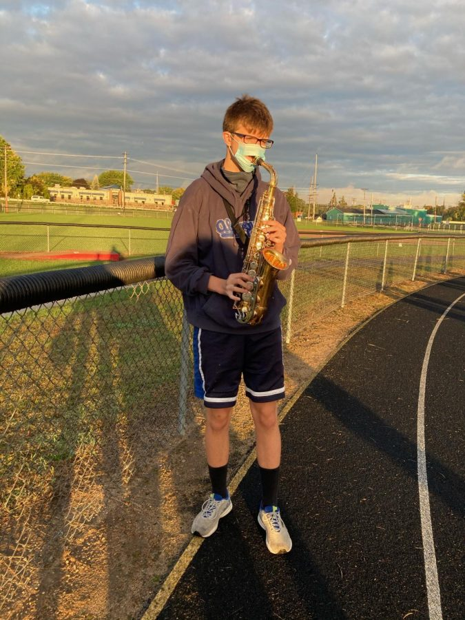 Saxophone player Matt Haag practices outisde with a mask on.