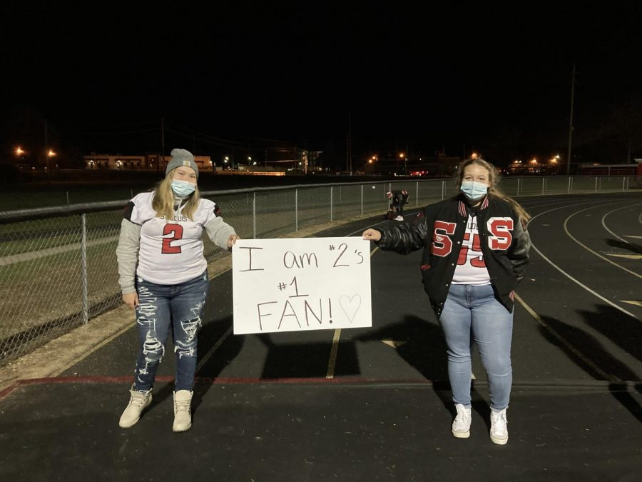 Delainee Zacharko (left) and Macie Salladay (right) stay six feet apart supporting SLHS football players.