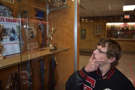 Aaron Bowerman strokes his mustache while admiring the 2005 cross country State champions trophy.