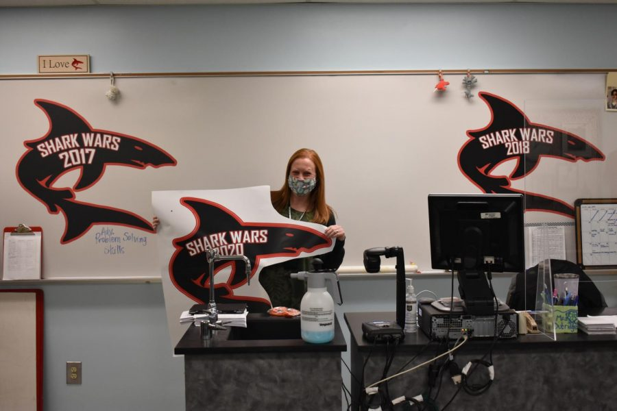 Mrs. Dubridge shows off her Shark Wars wins.