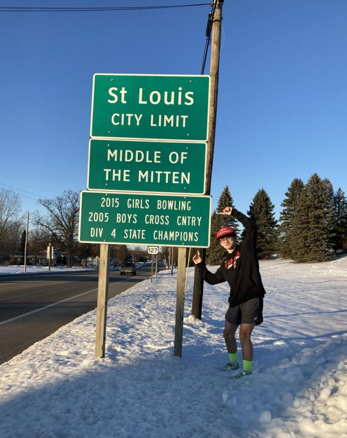 Craig Bebow, a member of the 2020 boys cross country team who won the Division Three State title, points at the sign that will soon display the teams win.
