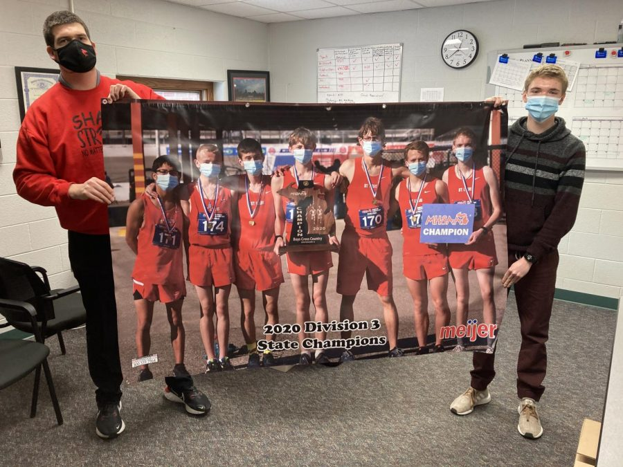 Athletic Director Bryan Anderson (left) and all-state member of the state championship team Keegan Honig (right) proudly hold up the banner graciously donated by Meijer.