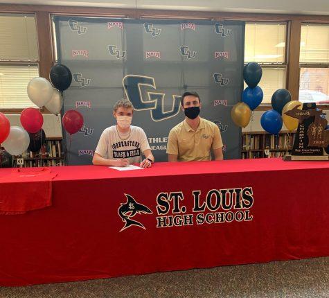 Keegan Honig (left) signs to run at Cornerstone with Coach Josh Neideck (right).