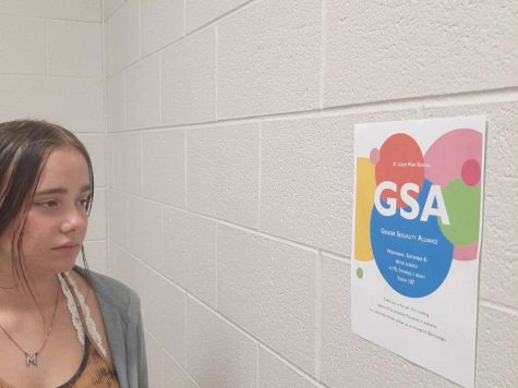 Mary Williams reads over the GSA flyer during passing time.