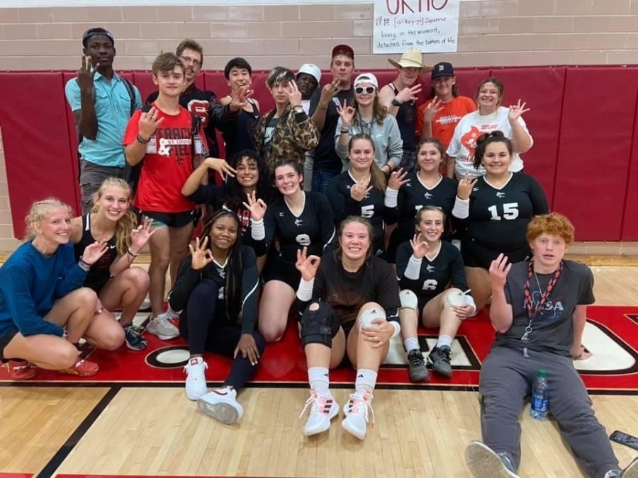 Varsity volleyball  pose with fellow classmates after a huge win!