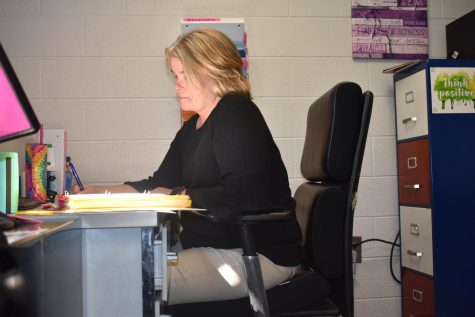 Mrs. Sura sits at her desk while working hard.
