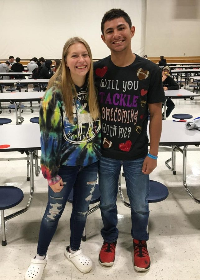 Martine Wiggins stands with his homecoming date, Kiersten Wenzlick, while wearing his hoco proposal shirt that reads Will you tackle homecoming with me?